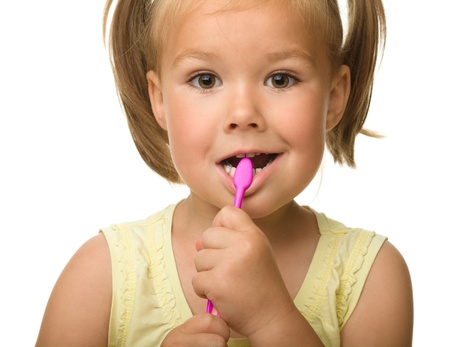 Cute little girl is cleaning teeth using toothbrush, isolated over white Stock Photo - 10055510