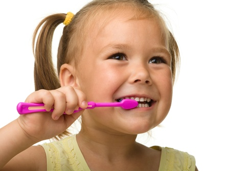 girl teeth: Cute little girl is cleaning teeth using toothbrush, isolated over white