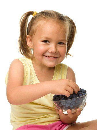 over eating: Cute cheerful little girl is eating blueberry, isolated over white Stock Photo