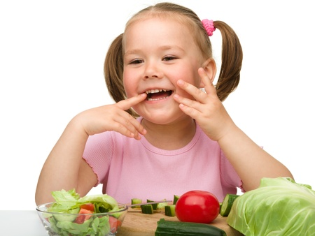Little girl is cutting carrot for salad using kitchen knife, isolated over white photo
