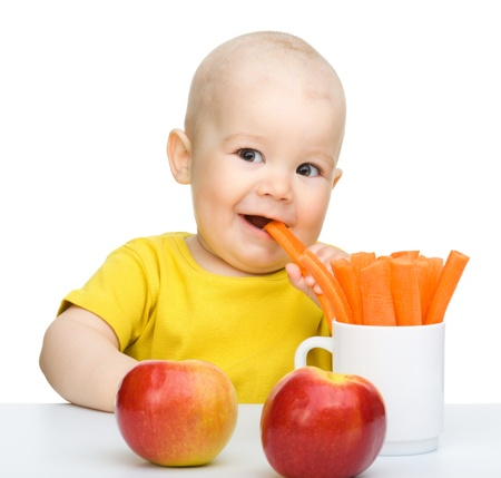 Cute little boy eats carrot and apples, isolated over white Stock Photo - 10055594