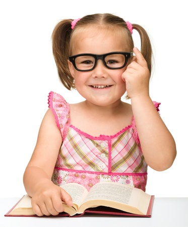Cute little girl wearing glasses is flipping over pages of a book, isolated on white