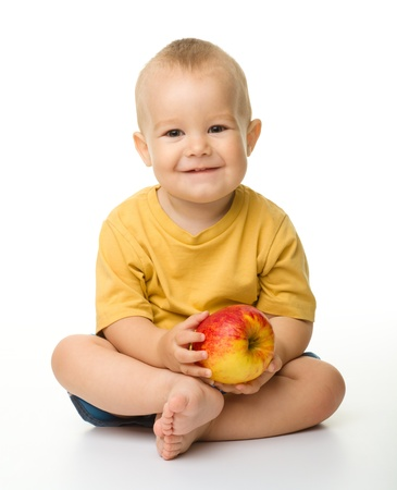 Cheerful little boy with red apple is smiling while sitting on a floor, isolated over white