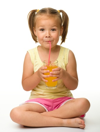 Cute little girl drinks orange juice using drinking straw while sitting on the floor, isolated over white Imagens