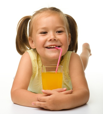 Cute little girl drinks orange juice using drinking straw while laying on the floor, isolated over white