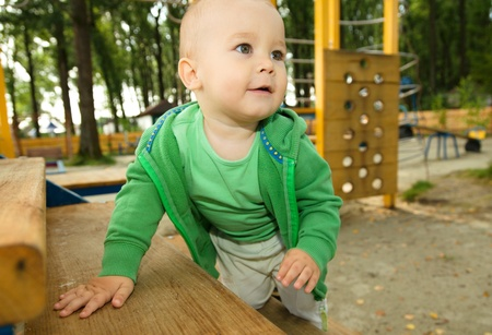 Cute little boy is playing on playground photo