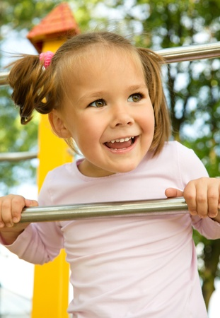 Cute little girl is playing in playground photo