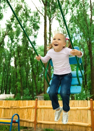 girl on swing: Cute cheerful little girl is swinging on swing