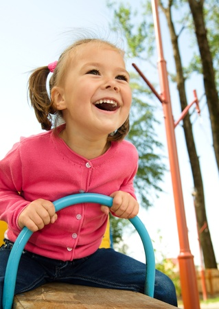 Happy little girl is swinging on see-saw Imagens