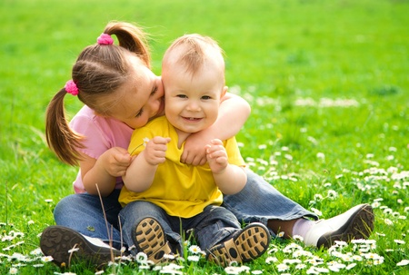Two children are sitting on green meadow and smile photo