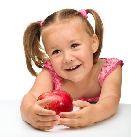 hungry kid: Portrait of a cute cheerful little girl with red apple, isolated over white Stock Photo