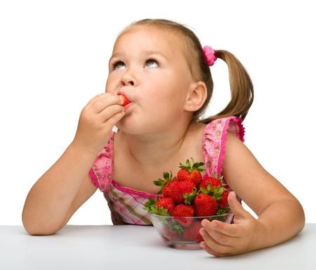 kid eat: Happy little girl eats strawberries, isolated over white Stock Photo