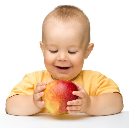 Cute little child is biting red apple while sitting at table, isolated over white photo