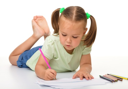 writing activity: Cute little girl is drawing while laying on the floor, isolated over white