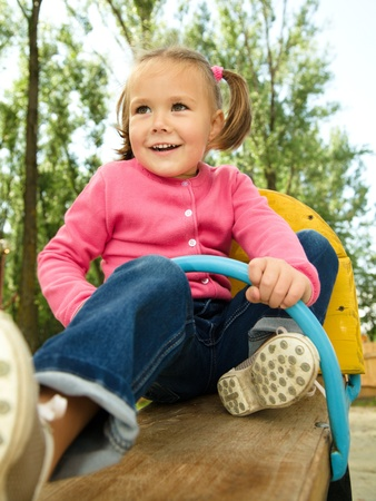 Happy little girl is swinging on see-saw photo