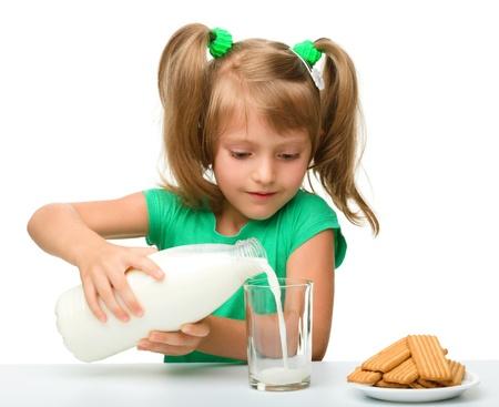 merenda: Cute bambina sta versando il latte in vetro, isolato su bianco Archivio Fotografico