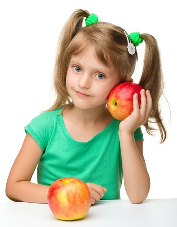 Portrait of a cute cheerful little girl with two red apples, isolated over white