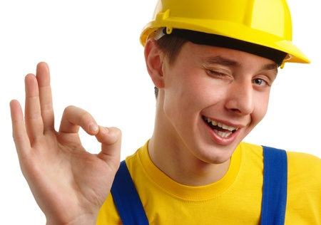 Young construction worker showing OK hand sign, isolated over white photo