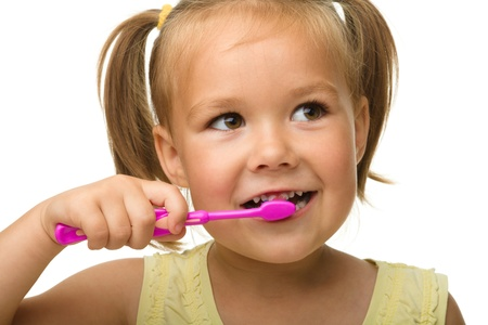 tooth cleaning: Cute little girl is cleaning teeth using toothbrush, isolated over white