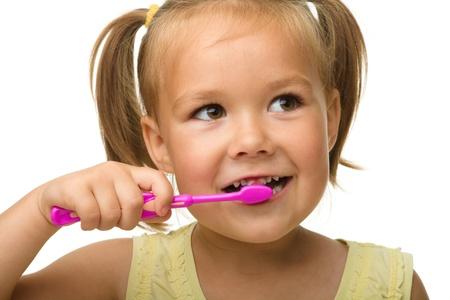 dientes sanos: Linda ni�a es limpieza de dientes usando cepillo de dientes, aislado en blanco