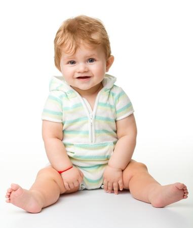infante: Ni�o feliz est� sentado en el piso, aislado en blanco Foto de archivo