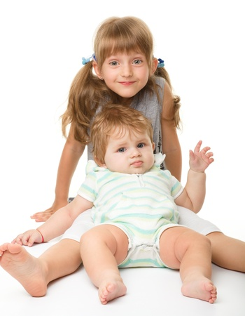 Two children (a girl and a boy) are having fun while sitting on floor, isolated over white Stock Photo - 10346070