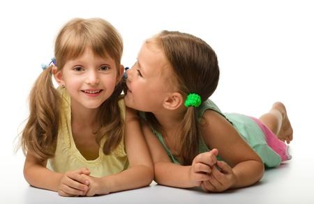 niños platicando: Dos niñas están charlando, aislado en blanco Foto de archivo