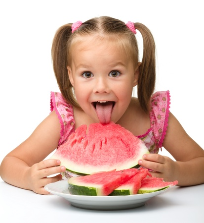 Cute little girl is gungy to eat watermelon, isolated over white Stock Photo - 10346102
