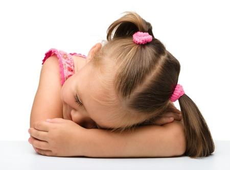 enfant qui dort: Petite fille dort à table pose sa tête sur les mains, isolés sur blanc