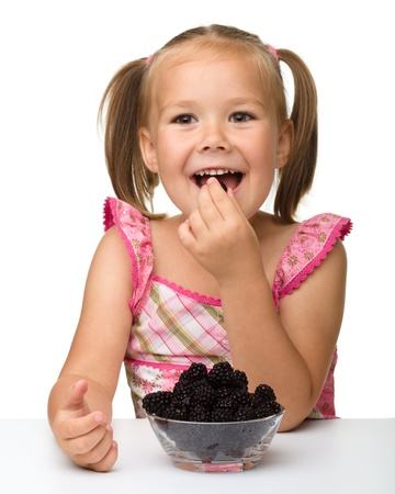 Cute cheerful little girl is eating blackberry, isolated over white photo