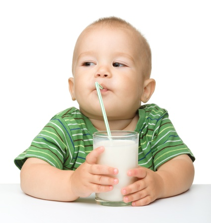 Cute little boy is drinking milk using drinking straw while sitting at table, isolated over white photo