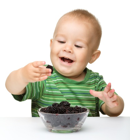 Cute cheerful little boy is eating blackberry, isolated over white photo