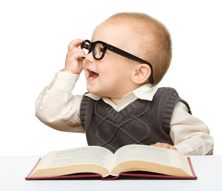 learning to read: Cute little child play with book and glasses while sitting at table, isolated over white