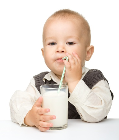tomando leche: Ni�ito lindo es beber leche con paja beber mientras estaba sentado a la mesa, aislada en blanco
