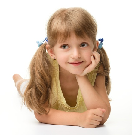 cute little girl smiling: Portrait of a cute happy little girl laying on floor, isolated over white Stock Photo