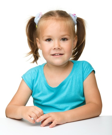 little table: Happy little girl is sitting at the table, isolated over white Stock Photo