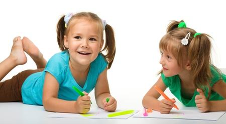 dessin enfants: Deux petites filles dessiner avec des marqueurs tout en posant sur le plancher, isol� sur blanc