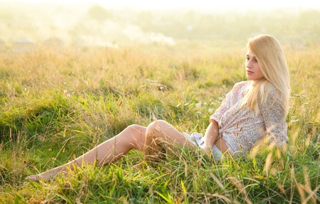 Beautiful girl is relaxing while sitting on green field photo