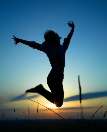 excitment: Silueta de una hermosa niña saltando por encima de la puesta del sol Foto de archivo