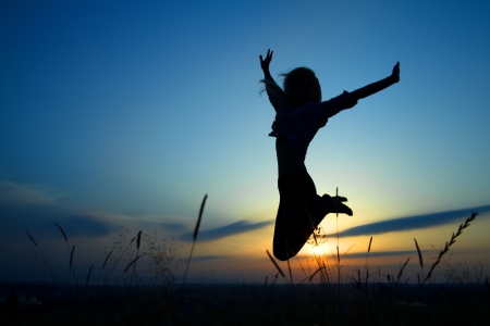 feeling positive: Silhouette of a beautiful girl jumping over sunset Stock Photo