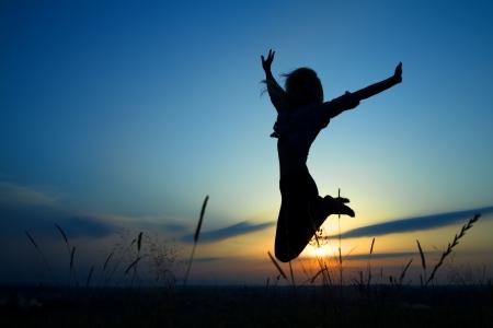 brincando: Silueta de una hermosa ni�a saltando sunset