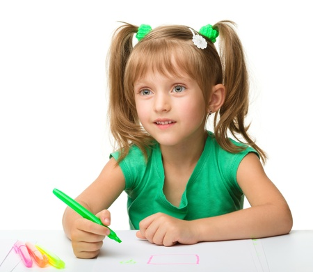 drawing table: Cute little girl draws with markers while sitting at table, isolated over white