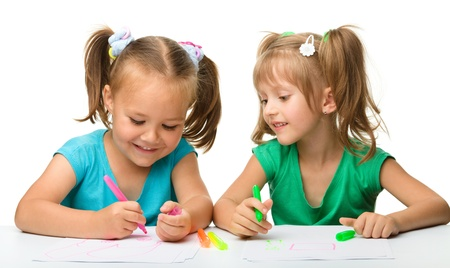 kids activities: Two little girls draw with markers while sitting at table, isolated over white