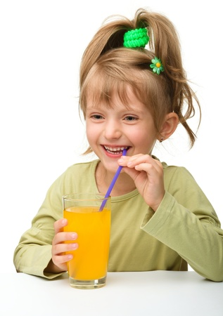 Cute little girl is drinking orange juice from one glass using straw, isolated over white photo