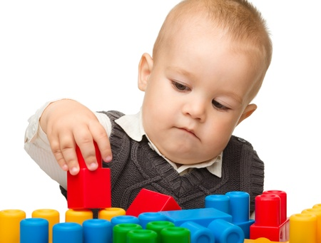 Cute little boy is playing with building bricks while sitting at the table, isolated over white Stock Photo - 10580298