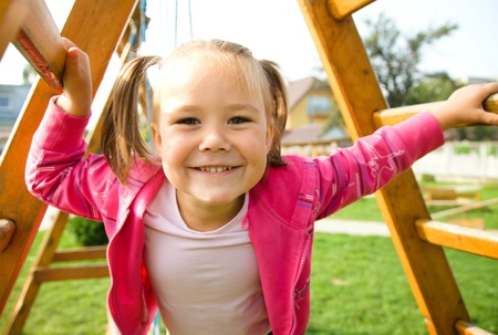 Portrait of a cute little girl playing on playground photo