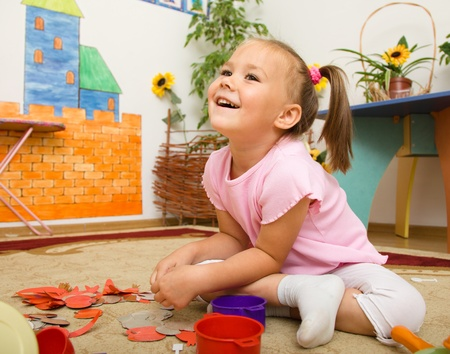 Cute little girl is playing in preschool while sitting on floor photo