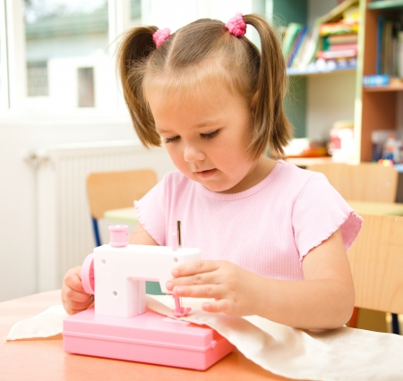 Cute little girl is playing with sewing machine in preschool Stock Photo - 10580277