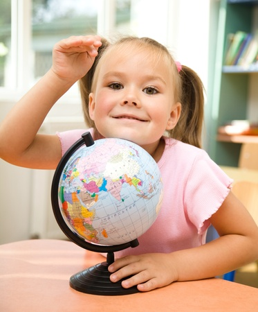 Little girl is playing with globe in preschool photo
