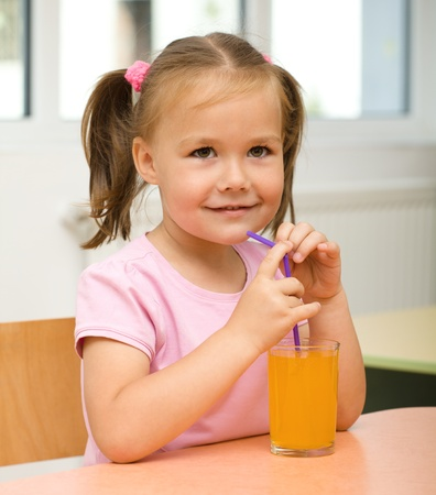 Cute cheerful little girl is drinking orange juice using straw photo